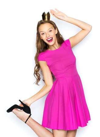 girl pose: people, holidays and fashion concept - happy young woman or teen girl in pink dress and princess crown
