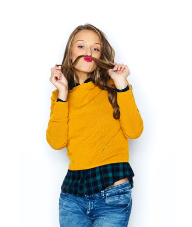 casting: people, style and fashion concept - happy young woman or teen girl in casual clothes having fun making mustache of her hair strand