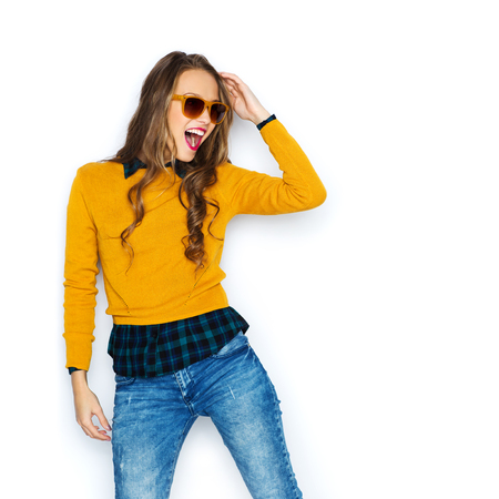 trendy: people, style and fashion concept - happy young woman or teen girl in casual clothes and sunglasses having fun