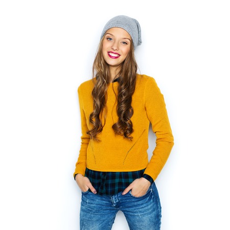people, style and fashion concept - happy young woman or teen girl in casual clothes and hipster hat Stockfoto