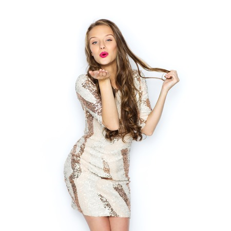 bacio: la gente, lo stile, le vacanze, acconciatura e concetto di moda - felice giovane donna o adolescente ragazza in abito fantasia con paillettes e capelli ondulati lunghi invio colpo bacio Archivio Fotografico