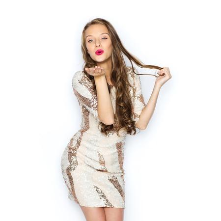 mensen, stijl, vakantie, kapsel en mode-concept - gelukkige jonge vrouw of tiener meisje in kostuum met pailletten en lang golvend haar verzenden slagkus Stockfoto