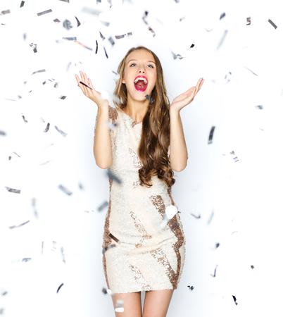 празднование: люди, праздники, эмоции и понятие гламур - счастливая молодая женщина или подросток девушка в маскарадном платье с блестками и конфетти на вечеринке