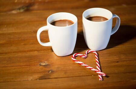 chocolate candy: holidays, christmas, winter, food and drinks concept - close up of candy canes and cups with hot chocolate or cocoa drinks on wooden table
