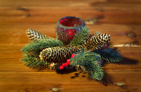 table decoration: christmas, decoration, holidays and new year concept - close up of natural fir branch decoration and fir-cone and candle in lantern on wooden table