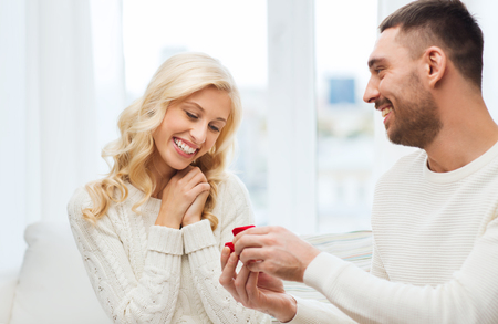 proposing: love, couple, relationship, proposal and holidays concept - happy man giving engagement ring in little red gift box to woman at home