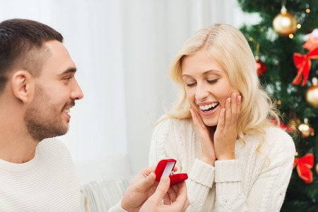 diamond ring: love, christmas, couple, proposal and people concept - happy man giving diamond engagement ring in little red box to woman at home Stock Photo