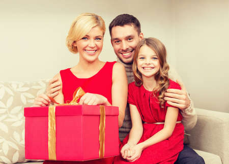 christmas winter: family, christmas, x-mas, winter, happiness and people concept - happy family opening Stock Photo