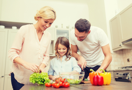 families: food, family, hapiness and people concept - happy family making dinner in kitchen Stock Photo