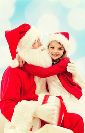 children santa claus: holidays, christmas, childhood and people concept - smiling little girl hugging with santa claus over blue lights background