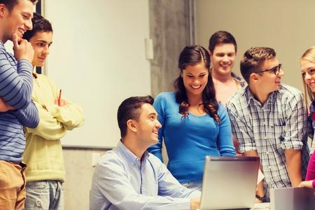 La educación, la escuela secundaria, la tecnología y concepto de la gente - grupo de estudiantes sonrientes y profesor de papeles, ordenador portátil en el aula Foto de archivo - 50816552