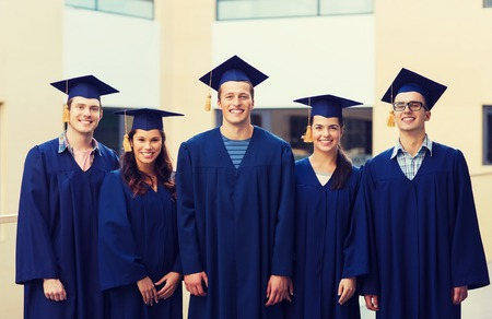 college campus: education, graduation and people concept - group of smiling students in mortarboards and gowns outdoors