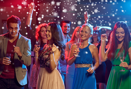 nonalcoholic beer: new year party, holidays, celebration, nightlife and people concept - smiling friends clinking glasses of non-alcoholic champagne and beer in club and snow effect