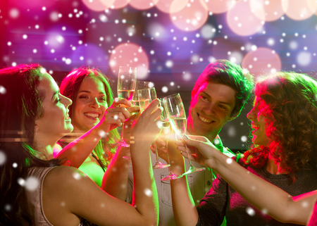 champagne glasses: new year party, holidays, celebration, nightlife and people concept - smiling friends with glasses of non-alcoholic champagne in club and snow effect Stock Photo