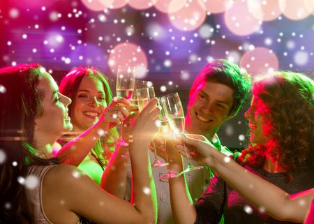 gente celebrando: partido del año nuevo, días de fiesta, celebración, vida nocturna y la gente concepto - amigos sonrientes con copas de champán sin alcohol en el club y la nieve efecto