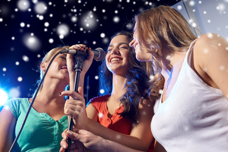 karaoke: party, holidays, celebration, nightlife and people concept - happy young women singing karaoke in night club and snow effect Stock Photo
