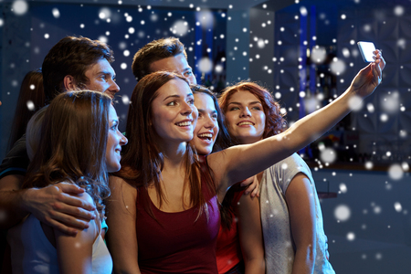 happy teens: party, technology, nightlife and people concept - smiling friends with smartphone taking selfie in club and snow effect Stock Photo