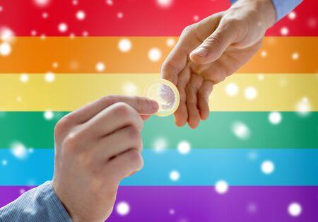 educacion sexual: personas, homosexualidad, sexo seguro, la educación sexual y el concepto de la caridad - Cerca de feliz pareja manos de los homosexuales varones que dan condón sobre el arco iris fondo de la bandera y el efecto de la nieve