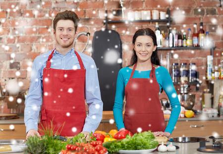 kulinarne: Klasa gotowanie, kulinarne, jedzenie i ludzie koncepcja - szczęśliwa para w kuchni nad efektem śniegu Zdjęcie Seryjne