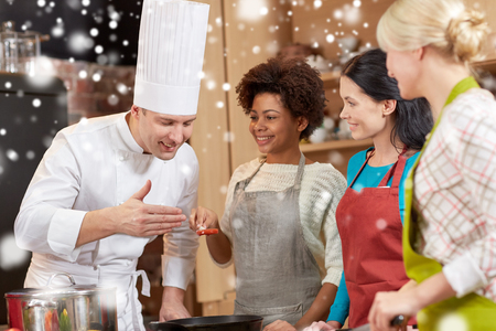 degustating: cooking class, culinary, food and people concept - happy group of women and male chef cook cooking in kitchen over snow effect