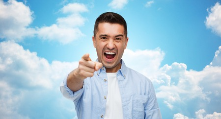 anger, emotions, aggression, gesture and people concept - angry man shouting and pointing finger on you over blue sky and clouds background