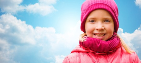 cloudy sky: autumn, childhood, happiness and people concept - happy beautiful little girl portrait outdoors over blue sky background