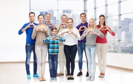 gesture, family, generation and people concept - group of smiling men, women and boy showing heart shape hand sign over empty office room or home