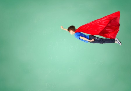 educaton: freedom, childhood, education, movement and people concept - boy in red superhero cape and mask flying in air over green school chalk board background