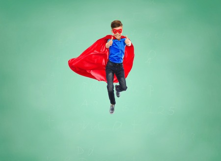 educaton: education, gesture, childhood, and people concept - boy in red super hero cape and mask flying in air and showing thumbs up over green school chalk board background