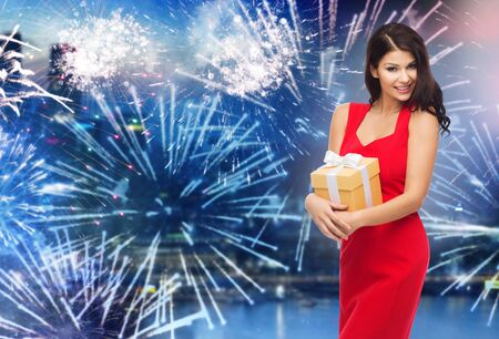 red dress: people, holidays, christmas, new year party and celebration concept - beautiful sexy woman in red dress with gift box over night city and firework background