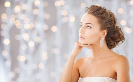 jewel hands: people, holidays, wedding, jewelry and luxury concept - beautiful woman wearing shiny diamond earrings over lights background