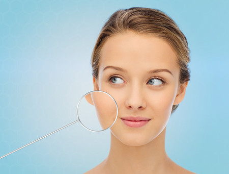 magnifying glass: beauty, people and health concept - smiling young woman face over blue background with magnifier showing perfect skin Stock Photo