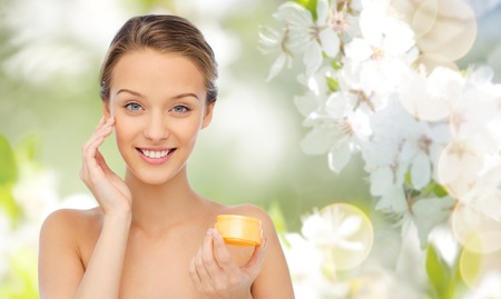 beauty, people, cosmetics, skincare and cosmetics concept - happy young woman applying cream to her face over summer green natural background with cherry blossom Banco de Imagens