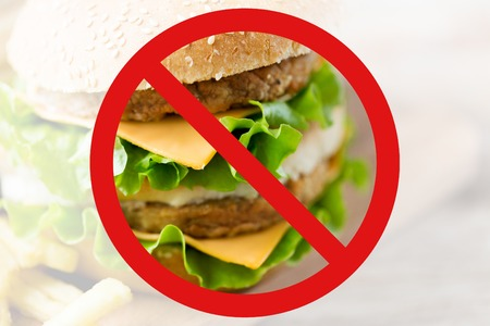 low carb diet: fast food, low carb diet, fattening and unhealthy eating concept - close up of hamburger or cheeseburger behind no symbol or circle-backslash prohibition sign