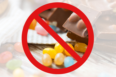 low carb diet: low carb diet, fattening and unhealthy eating concept - close up of jelly beans candies and chocolate behind no symbol or circle-backslash prohibition sign