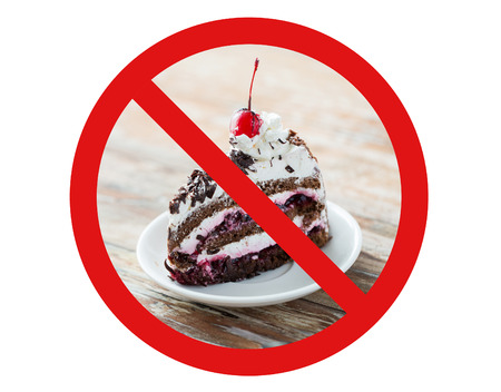fattening: low carb diet, fattening and unhealthy eating concept - piece of delicious cherry chocolate layer cake on saucer with spoon behind no symbol or circle-backslash prohibition sign