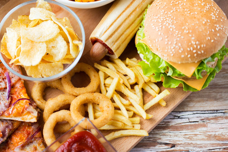 food dish: fast food and unhealthy eating concept - close up of hamburger or cheeseburger, deep-fried squid rings, french fries hotdog and potato chips on wooden table top view