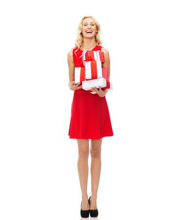 elegant girl: people, christmas, birthday and holidays concept - happy young woman in red dress holding gift boxes