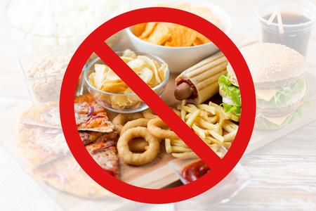 Fast Food, Low-Carb-Diät, Mast- und ungesunde Ernährung Konzept - in der Nähe von Fast-Food-Snacks und Cola-Getränk auf Holztisch hinter kein Symbol oder kreis Backslash Verbotsschild nach oben Standard-Bild