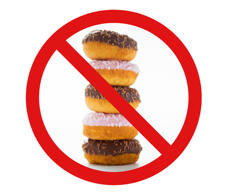 low carb diet: fast food, low carb diet, fattening and unhealthy eating concept - close up of glazed donuts pile over white behind no symbol or circle-backslash prohibition sign