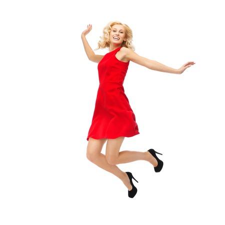 jumping: la gente, el movimiento, la felicidad y el concepto de vacaciones - mujer joven feliz en el vestido rojo que salta arriba en el aire