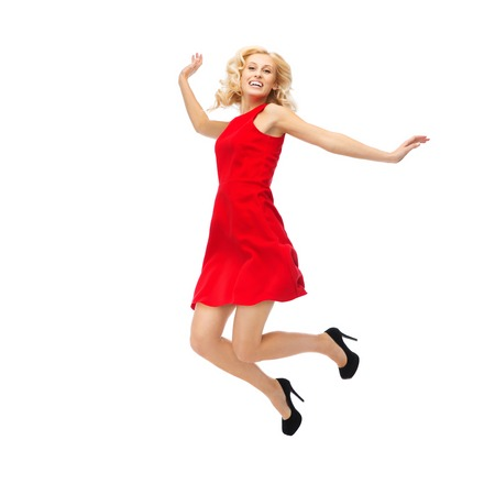 joy: people, motion, happiness and holidays concept - happy young woman in red dress jumping high in air Stock Photo