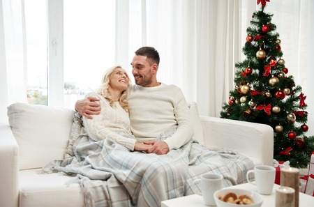family sofa: family, christmas, holidays, love and people concept - happy couple covered with plaid sitting on sofa at home
