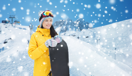 leisure activities: winter, leisure, sport and people concept - happy young woman in ski goggles with snowboard over snow and mountain background