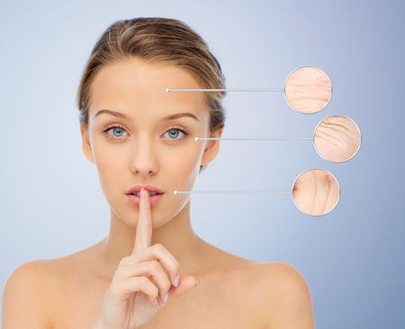 aging face: people, gesture, aging and beauty concept - beautiful young woman holding finger on lips with magnifier showing wrinkles on her face over violet background
