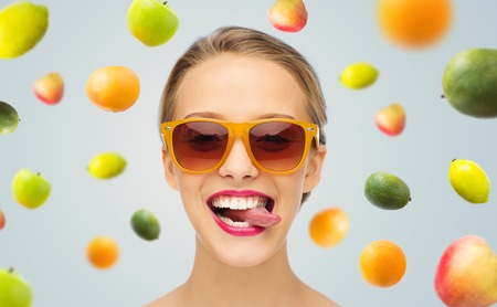 female tongue: people, expression, joy and fashion concept - smiling young woman in sunglasses with pink lipstick on lips showing tongue