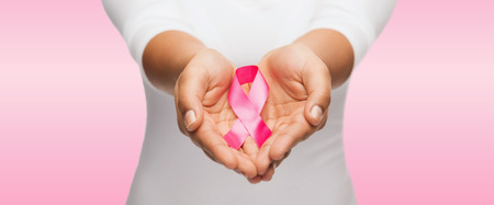 Gesundheit und Medizin Konzept - Womans Hände hält rosa Brustkrebsbewusstseinsband