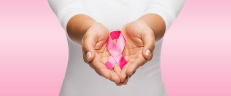 sanità e della medicina concetto - womans mani azienda seno rosa consapevolezza del cancro nastro