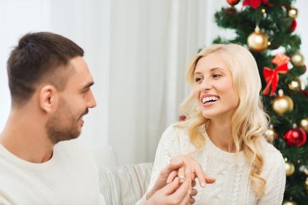 amor, navidad, pareja, propuesta y concepto de la gente - anillo de compromiso de diamantes hombre feliz dando a la mujer en el hogar