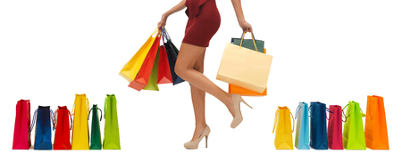high heeled shoes: people, sale and consumerism concept - close up of woman in red short skirt and high heeled shoes with shopping bags Stock Photo